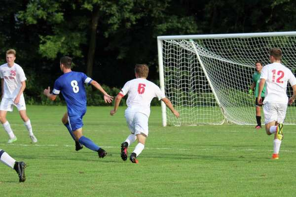 Darien's Sean Gallagher looks to weave his way through several Greenwich defenders. Gallagher had the assist on a corner kick for the lone goal in the contest.
