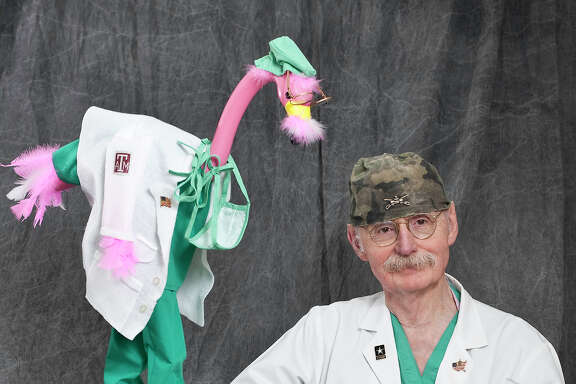Dr. Red Duke poises with award-winning flamingo, dressed to look like him.