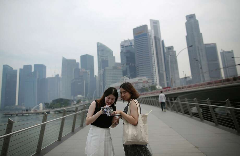 Tourists look at photographs taken on their smartphones in front of a hazy financial skyline on Friday, Aug. 26, 2016 in Singapore. Singapore's air quality deteriorated to unhealthy levels on Friday as winds blew smoke from fires on Sumatra across the city-state and southern Malaysia. (AP Photo/Wong Maye-E) Photo: Wong Maye-E, Associated Press