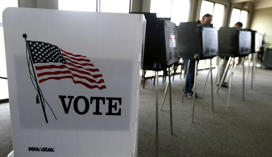 FILE - In this March 18, 2014 file photo, voters cast their ballots in the Illinois primary in Hinsdale, Ill. Republicans have gained ground on Democrats' strength in registering voters in three battleground states _ and kept their razor-thin advantage in Iowa, offering some hope for Donald Trump and raising the stakes over ballot access in the final weeks before Election Day. (AP Photo/M. Spencer Green, File) Photo: M. Spencer Green, Associated Press