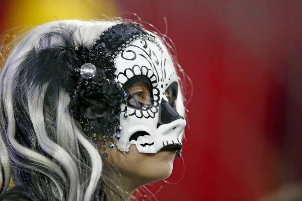 An Oakland Raiders fan watches her team warm up prior to an NFL preseason football game against the Arizona Cardinals Friday, Aug. 12, 2016, in Glendale, Ariz.  The Raiders defeated the Cardinals 31-10. (AP Photo/Ross D. Franklin)