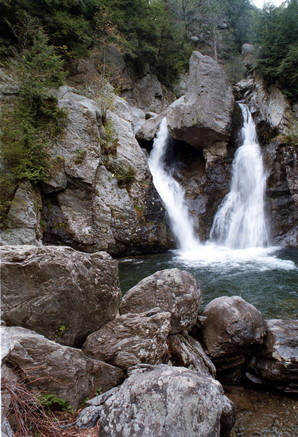 ** FILE **--Bash Bish Falls is shown in Mount Washington, Mass., in this May 10, 1999, file photo. Bash Bish, on the border with New York state, is a hidden getaway in the Berkshire Mountains. The scenic waterfall, which plunges 60 feet over moss and fern-decked rocks into a clear rock-rimmed pool, is one of the most dramatic and most photographed in the state. The town of Mount Washington is preparing to close the only road entering the area from the Massachusetts side because it can not afford to fixthe badly worn road. (AP Photo/The Berkshire Eagle, Ben Garver)