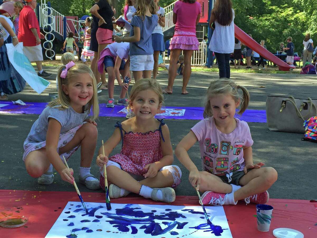 """(L-R): ISD Kindergarteners Alexia Lisjak, Cameron Dionis and Eve Woodward helped paint world flag posters for the school's first annual 5K Around the World Run and Kids Obstacle Course at a 5K """"prep rally"""" on Sept. 16, 2016."""