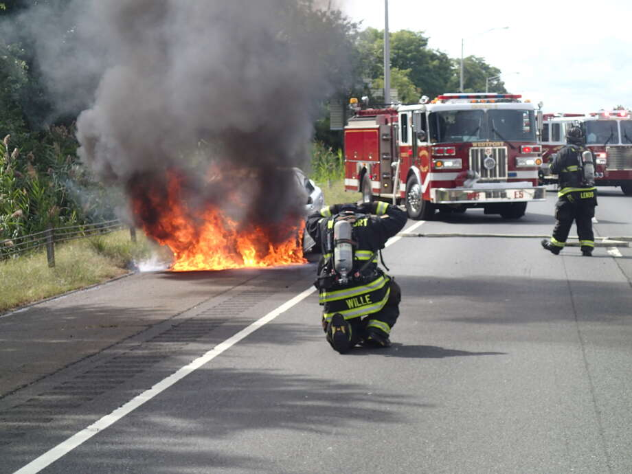 Westport firefighters put out a car fire in the northbound breakdown lane of I-95 on the afternoon of Sept. 20, 2016. The car was between exits 17 and 18 in Westport, Conn. Photo: Westport Fire Department / Contributed Photo / Westport News