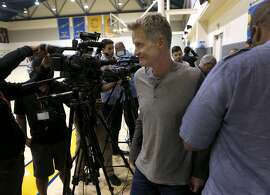 Golden State Warriors head coach Steve Kerr walks past a group of sports reporters and cameras after discussing the upcoming NBA season at the team's practice facility in Oakland, Calif. on Wednesday, Sept. 21, 2016.
