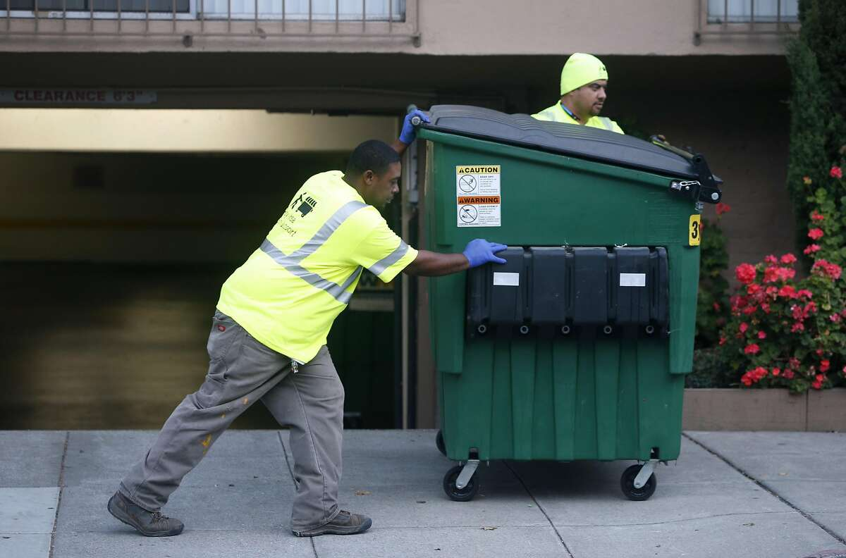 Alvin Hughes III (left) and Junior Fiame push a trash dumpster to the sidewalk in front of a large apartment building on Alice Street before the contracted garbage collector arrives in Oakland, Calif. on Wednesday, Sept. 14, 2016. Bay Area Bin Service provides push-pull service of dumpsters and recycle bins for large residential and commercial clients at a fraction of the cost charged by the contracted garbage collection company Waste Management.