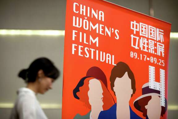 In this Sept. 17, 2016 photo, a participant walks past a banner for the China Women's Film Festival during its opening ceremony in Beijing. Campaigners are highlighting gender inequality in film at the China Women's Film Festival that runs until Sunday, Sept. 25 in Beijing. (AP Photo/Mark Schiefelbein)