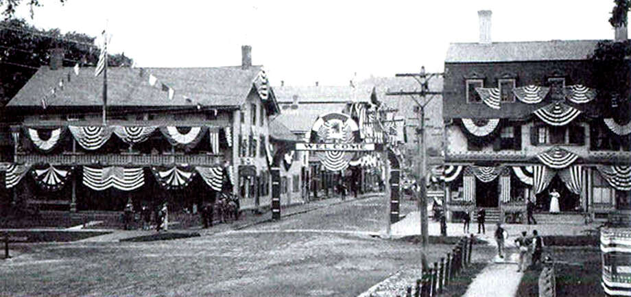 """As viewed likely from the steps of the Village Hardware on the east side of the Village Green, New Milford is dressed up for the firemen's parade celebrating the turn of the century to 1900. Two years later, the Great Fire was to destroy much of what appears in this photograph of the intersection of Main and Bank streets. The United States Hotel, right, survived the fire while the New England House Hotel, left, did not. Photo: Courtesy Of """"Howard Peck's New Milford"""" / The News-Times Contributed"""
