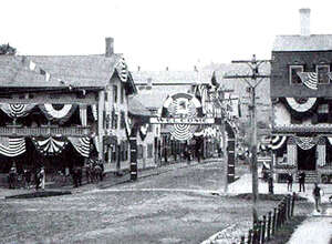 As viewed likely from the steps of the Village Hardware on the east side of the Village Green, New Milford is dressed up for the firemen's parade celebrating the turn of the century to 1900. Two years later, the Great Fire was to destroy much of what appears in this photograph of the intersection of Main and Bank streets. The United States Hotel, right, survived the fire while the New England House Hotel, left, did not.