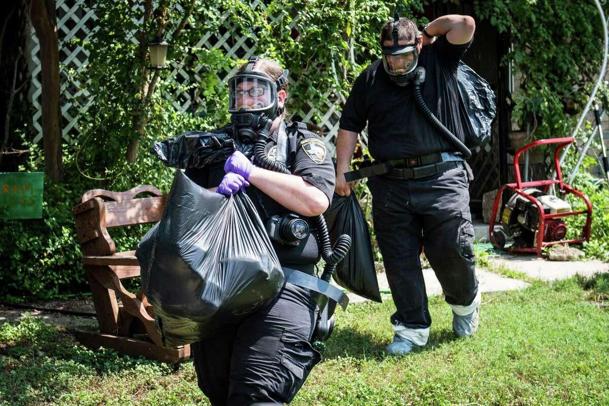 San Antonio Animal Care Services cruelty officers Kateri Miller, left, and Joey Cortez, right, remove the bodies of four dead dogs found in the refrigerator of a house in Southwest San Antonio on Wednesday, September 21, 2016. Lisa Norwood of San Antonio's Animal Care Services said that they removed 54 animalsÐincluding 43 dogs, cats, and a parrotÐin total from the house in the 8000 block of Big Creek Drive on the Southwest side of San Antonio. The home's owner, Jacqueline Paniagua, said that she had been keeping the dogs as a foster owner but that the service center she was receiving animals from stopped responding to her calls and providing assistance. She left the animals in the care of someone else while she was away for two weeks recently and returned once she received a call from the city's animal services.
