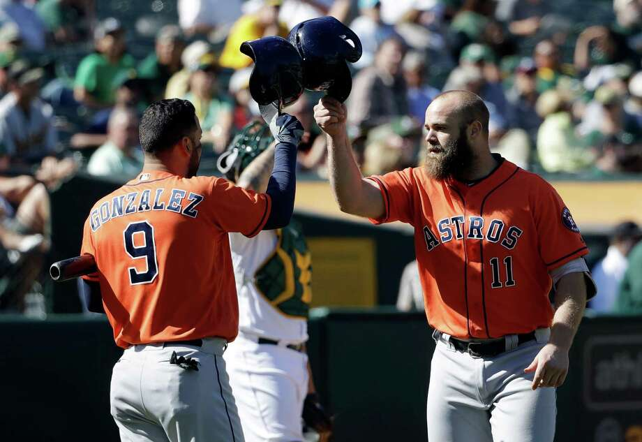 Houston Astros' Evan Gattis, right, celebrates his solo home run with teammate Marwin Gonzalez (9) during the eighth inning of a baseball game against the Oakland Athletics, Wednesday, Sept. 21, 2016, in Oakland, Calif. (AP Photo/Marcio Jose Sanchez) Photo: Marcio Jose Sanchez, Associated Press / Copyright 2016 The Associated Press. All rights reserved.