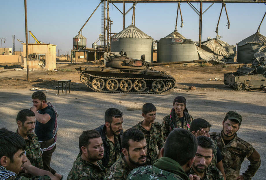 Kurdish fighters walk by tanks in 2015 used by Islamic State after a battle near Tel Tamer, Syria. Photo: MAURICIO LIMA / Mauricio Lima / New York Times 2015 / NYTNS