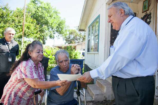 Tax Assessor-Collector Albert Uresti, hands Angelita and Frank Juarez property tax refund checks at their home Tuesday June 9, 2015. The checks were a result of the Tax Office's efforts to secure a residential homestead exemption reinstatement and the granting of a 65 and over exemption from the Bexar Appraisal District.