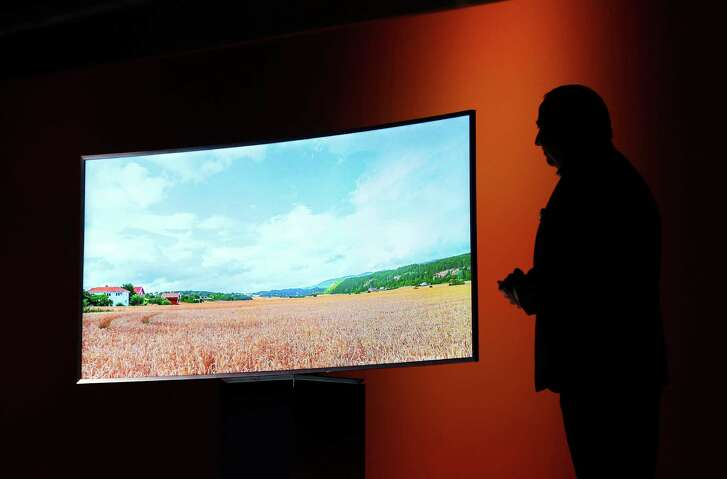 A Samsung executive introduces a Samsung SUHD 4K TV in 2015. An environmental group is accusing a trio of major TV makers of engineering their sets to make them look more energy-efficient than they actually are.
