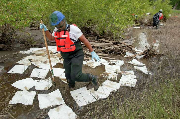 An oil spill worker for Oil Mop Emergency Response steps out of a ring of absorbent pads along a flood plain of the Yellowstone River in July 2011 near Laurel, Mont. A pipeline break spilled 63,000 gallons of oil into the river.