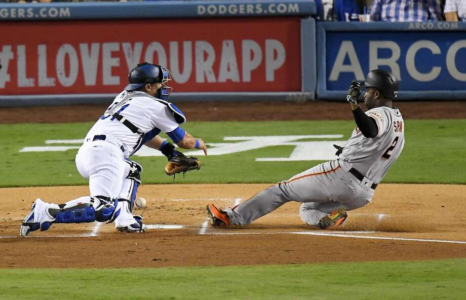 San Francisco Giants' Denard Span, right, scores on a single by Angel Pagan as Los Angeles Dodgers catcher Carlos Ruiz, left, drops the ball the play during the first inning of a baseball game, Wednesday, Sept. 21, 2016, in Los Angeles. (AP Photo/Mark J. Terrill) Photo: Mark J. Terrill, Associated Press