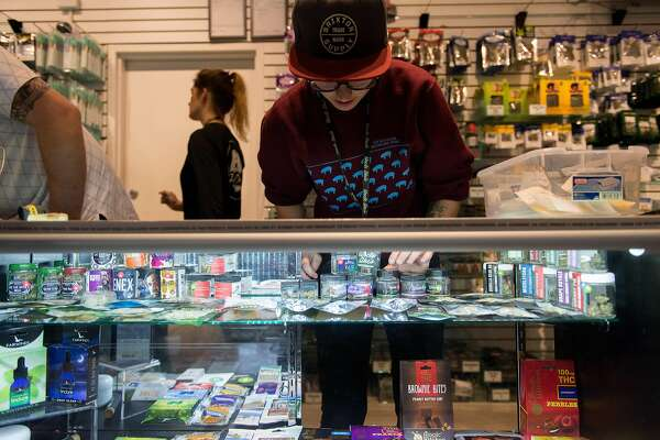 Budtender Evan Price, center, organizes a display case Sept. 20, 2016 at Uncle Ike's, a 21+ recreational marijuana store in the gentrifying Central District neighborhood of Seattle. The store sells the most marijuana of any in the state through heavy marketing and cheap prices, owner Ian Eisenberg said.