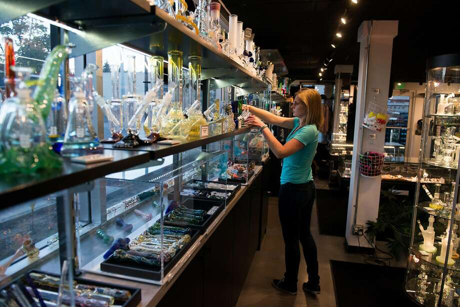 Floor Manager Zelda Miltner straightens up around Uncle Ike's sister glass shop, Glass and Goods. The store carries a variety of bongs and pipes and other smoking accessories, as well as the kind of branded merchandise that the main pot shop may not carry under state law. Photo: Daniel Berman, Special To The Chronicle