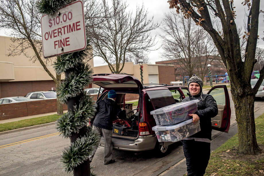 ERIN KIRKLAND | ekirkland@mdn.net FILE -- Tucker Mashue, 17, carries boxes of hats to the curb while setting up his booth at Midland's Winter Village on Dec. 17. Together Dennis Mashue and his son Tucker Mashue, 17, run Tuck's Tooques, a pro-autism microbusiness, which helps Dennis teach Tucker entrepreneurship skills by selling handmade Nepalese winter hats. / Midland Daily News