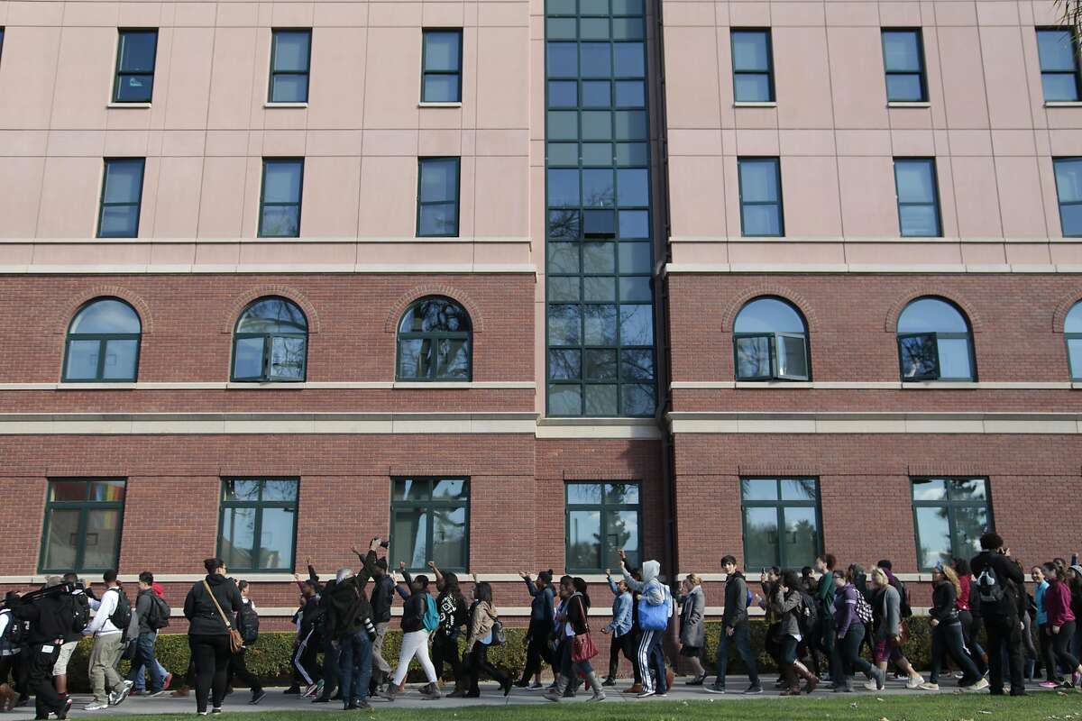 Protesters march past San Jose State University dormitories where a student was harassed by his roommates in San Jose, Calif. on Thursday, Nov. 21, 2013. A student on campus was a recent victim of a series of hate crimes committed by his roommates.