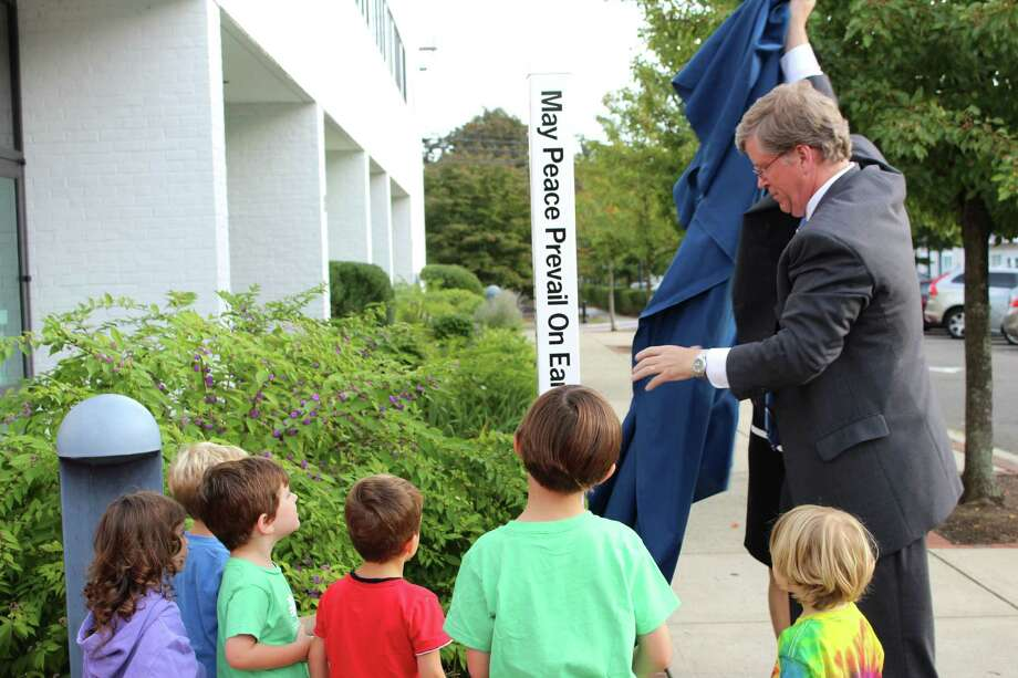 Second Selectman Michael Kaelin unveiled the first Peace Pole at Wilton Library on Tuesday, as part of the Wilton Rotary Club's community project. Eleven more will be planted at schools, businesses and town facilities. Photo: Stephanie Kim / Hearst Connecticut Media