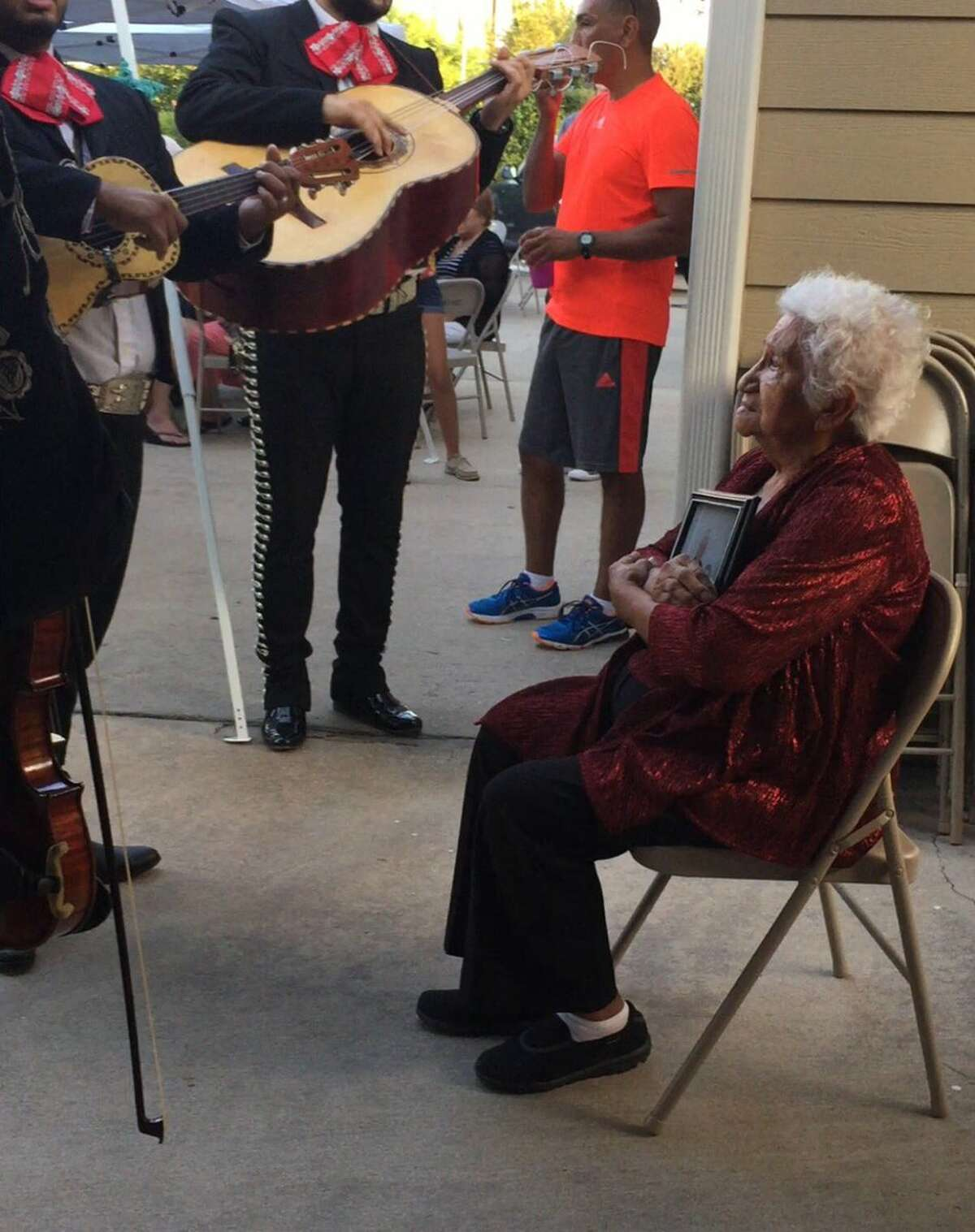 Josie Reza, 85, enjoying her mariachi serenade while holding a photo of her late husband on Sept. 17, 2016.