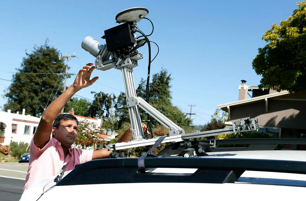 Anuj Gupta, co-founder of the Civil Maps augmented reality navigation system for autonomous vehicles, activates a LiDAR sensor on the roof of a car before conducting a road test in Albany, Calif. on Wednesday, Sept. 21, 2016.