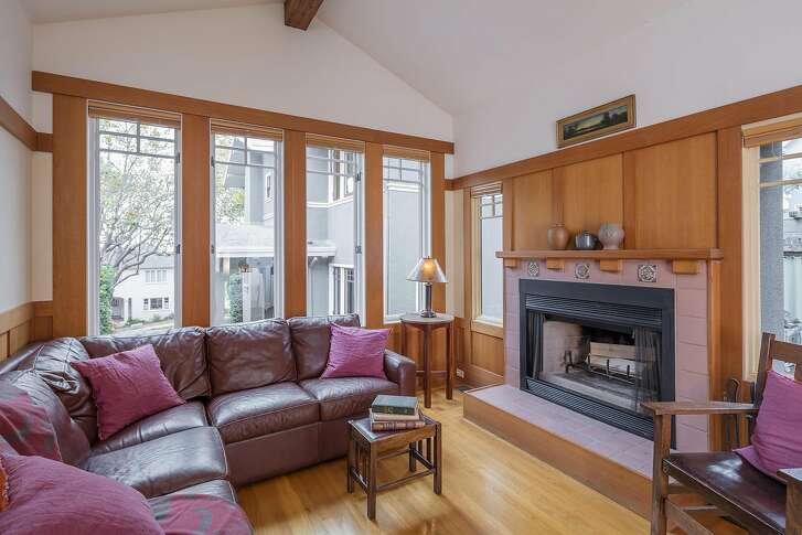 The cottage's living room is finished with a fireplace and tall wainscoting.