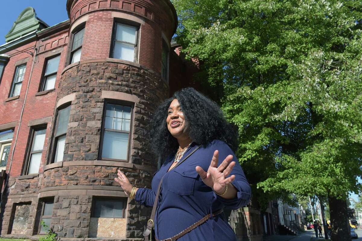 Taqiyyah Knight talks about the building at 2 Judson Street, background, on Tuesday, Sept. 13, 2016, in Albany, N.Y. This is one of the buildings that will be illuminated as part of the Breathing Lights project. Knight is hoping to buy the property from the land bank. (Paul Buckowski / Times Union)
