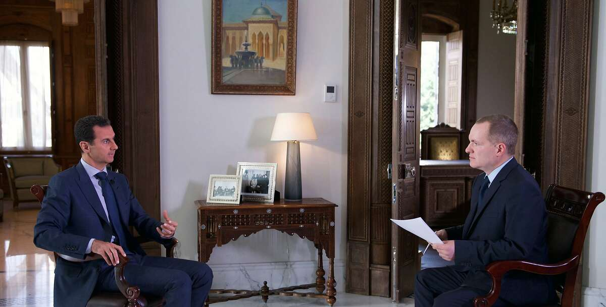 In this Wednesday, Sept. 21, 2016 photo released by the Syrian Presidency, Syrian President Bashar Assad, left, speaks to Ian Phillips, Vice President, International News for The Associated Press, at the presidential palace in Damascus. Assad said U.S. airstrikes on Syrian troops in the country�s east were �definitely intentional,� lasting for an hour, and blamed the U.S. for the collapse of a cease-fire deal brokered with Russia. In the interview with the AP, Assad said the war, now in its sixth year, is likely to �drag on� because of what he said was continued external support for his opponents. (Syrian Presidency via AP)