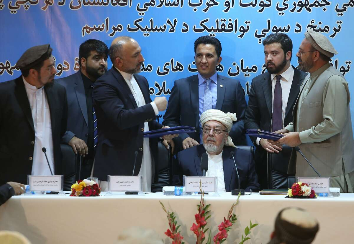 Amin Karim, representative of Gulbuddin Hekmatyar, right, and Afghanistan national security adviser Mohammad Hanif Atmar, third left, hold their documents after signing a peace deal, in Kabul, Afghanistan, Thursday, Sept. 22, 2016. The Afghan government has signed a draft peace deal with Hizb-i-Islami Gulbuddin, a designated �global terrorist� after lengthy negotiations that could pave the way for a similar accord with the Taliban. It grants full political rights to Gulbuddin's Hezb-i-Islami party and obliges the Afghan authorities to work to have it removed from the United Nations� list of foreign terrorist organizations. (AP Photo/Rahmat Gul)