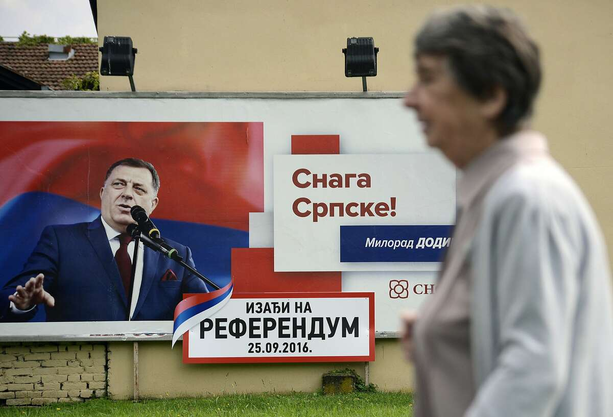 In this photo taken on Wednesday, Sep. 21, 2016. Bosnian woman passes by poster for Sundays referendum in the Bosnian town of Banja Luka, 240 kms (150 miles) northwest of the Bosnian capital of Sarajevo , Bosnia. Bosnia�s Serb mini-state is holding a referendum this weekend that has turned into a proxy political battle between the West and Russia, stoking ethnic tensions and triggering fears of new clashes more than 20 years after the end of the Balkans War. Sunday's vote asks residents of Republika Srpska whether to maintain a national holiday on Jan. 9, despite a ruling of Bosnia's constitutional court that the date discriminates against non-Serbs. (AP Photo/Radivoje Pavicic)