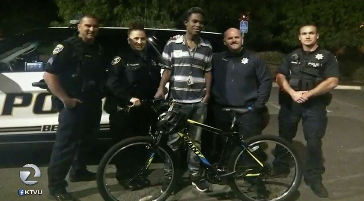 Jourdan Duncan seen posing with police after officers gifted him a bicycle to ease his commute to work.