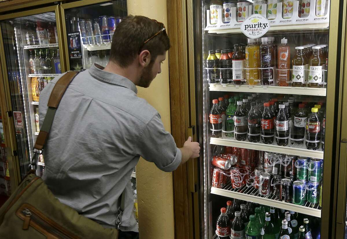 Ezra, last name not given, looks at the soft drink selection at K & D Market in San Francisco, Wednesday, Oct. 1, 2014. A tax on sodas and other sugar-laden drinks that voters and courts in other parts of the country have rejected is on the November ballots in San Francisco and Berkeley, two cities that have been open to such social-engineering initiatives in the past. (AP Photo/Jeff Chiu)