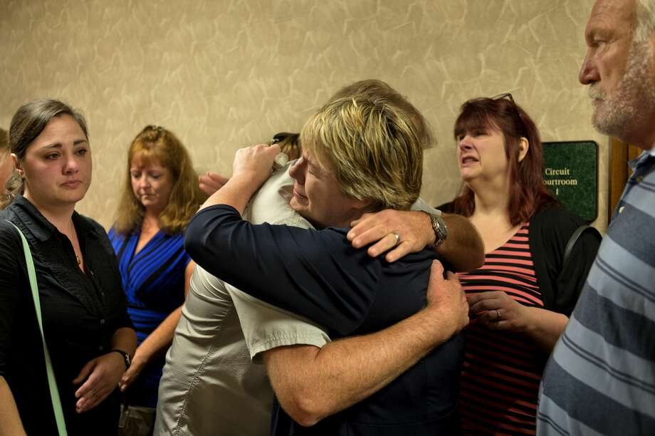 Craig Northrup, left, comforts Carrie Pajunen after Gregory Rose was sentenced 31-70 years in prison at the Midland County Circuit Court Thursday afternoon. Carrie's mother, Connie Pajunen, was killed and her body was found inside her burning home. Photo: Brittney Lohmiller/Midland Daily News/Brittney Lohmiller