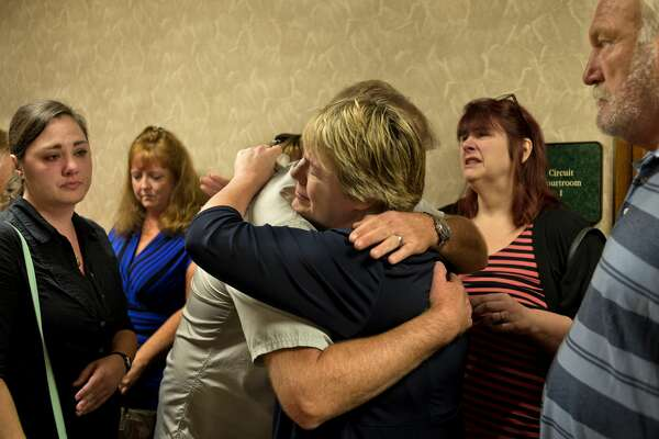 Craig Northrup, left, comforts Carrie Pajunen after Gregory Rose was sentenced 31-70 years in prison at the Midland County Circuit Court Thursday afternoon. Carrie's mother, Connie Pajunen, was killed and her body was found inside her burning home.