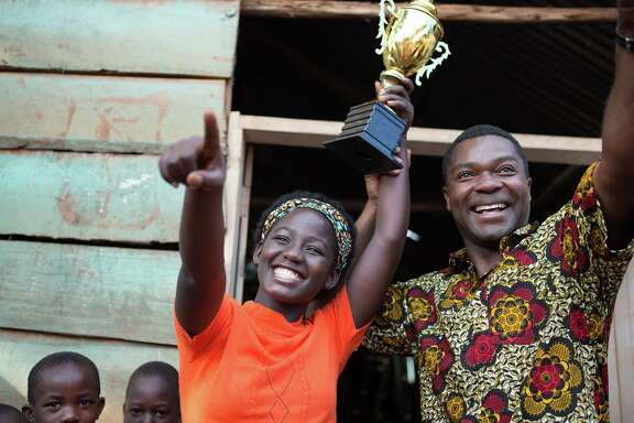 "In this image released by Disney, Madina Nalwanga, left, and David Oyelowo appear in a scene from ""Queen of Katwe."" (Edward Echwalu/Disney via AP)"