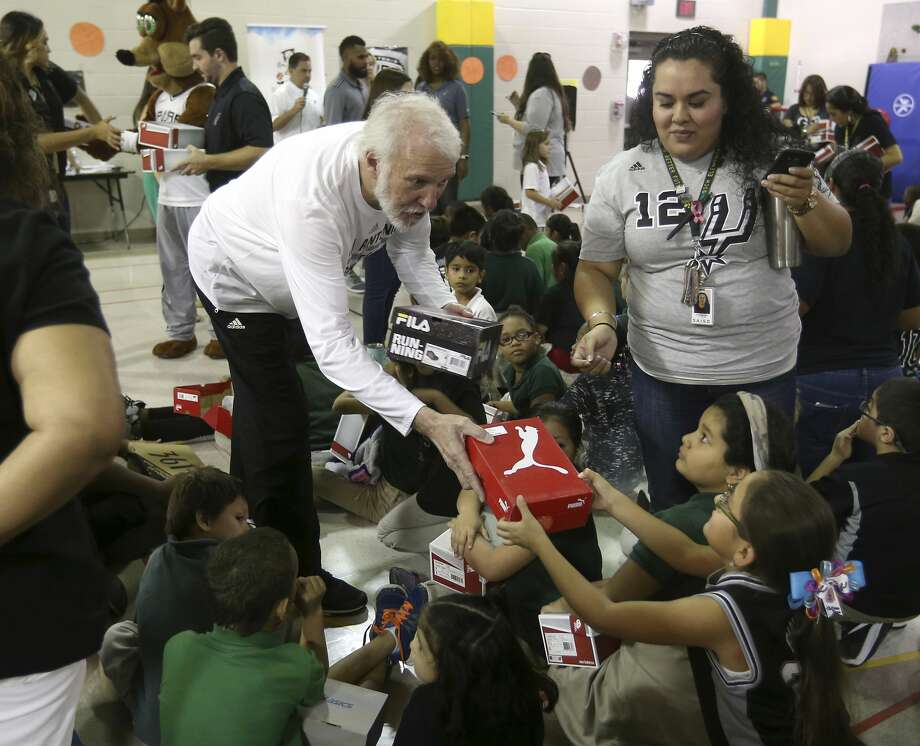 Spurs coach Gregg Popovich hands shoes out Thursday afternoon, Sept. 22, 2016 to children at Hirsch Elementary as part of a Shoes That Fit donation. About 200 children from the school received brand new shoes during the give-away. Photo: William Luther/San Antonio Express-News