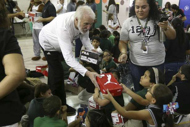 Spurs coach Gregg Popovich hands shoes out Thursday afternoon, Sept. 22, 2016 to children at Hirsch Elementary as part of a Shoes That Fit donation. About 200 children from the school received brand new shoes during the give-away.