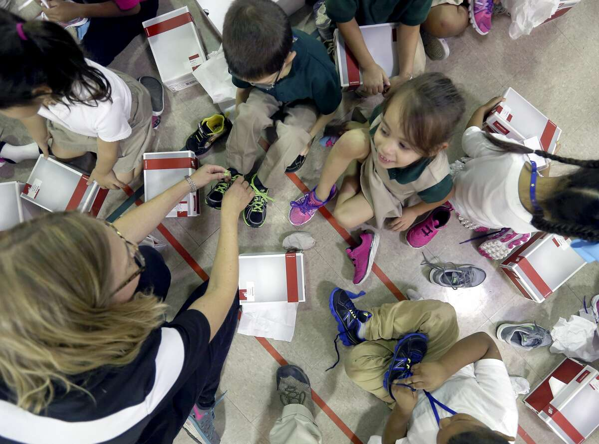 Hirsch Elementary School children put on new shoes Thursday afternoon, Sept. 22, 2016 moments after receiving the free footwear from the San Antonio Spurs and Shoes That Fit, a national, non-profit 501(c)3 organization based in Claremont, California. The organization is the nation?•s largest nonprofit provider of new athletic shoes to children in need according to a Spurs' press release about the event.