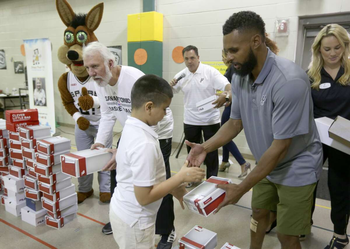 Spurs coach Gregg Popovich, left, and point guard Patty Mills, right, hand out shoes Thursday afternoon, Sept. 22, 2016 to children at Hirsch Elementary as part of a Shoes That Fit event. Shoes That Fit is a national, non-profit 501(c)3 organization based in Claremont, Calif., and is the nation?•s largest nonprofit provider of new athletic shoes to children in need according to a Spurs' press release.