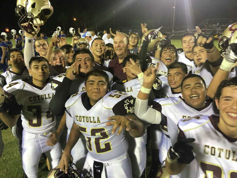 Cotulla players celebrate with coach Kelly Shull after beating Natalia last Friday night on the road. Photo: Roy Bragg / San Antonio Express-News