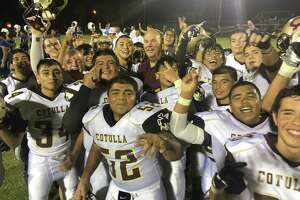 Cotulla players celebrate with coach Kelly Shull after beating Natalia last Friday night on the road.