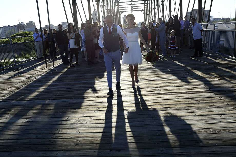 Devin Verdon and Suzie Verdon walk toward Dignowity Hill after their wedding ceremony on the Hays Street Bridge April 2, 2016. Photo: Lisa Krantz /San Antonio Express-News / SAN ANTONIO EXPRESS-NEWS