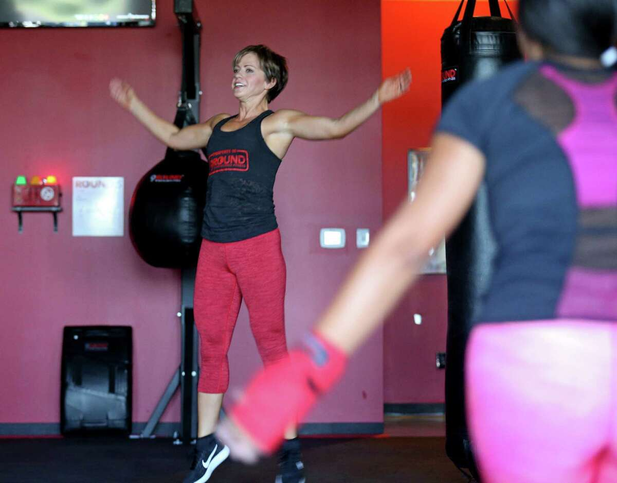 9Round Fitness owner Lori Peery (center) performs jumping jack.