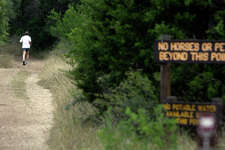 A jogger heads down a trail at Government Canyon State Natural Area.