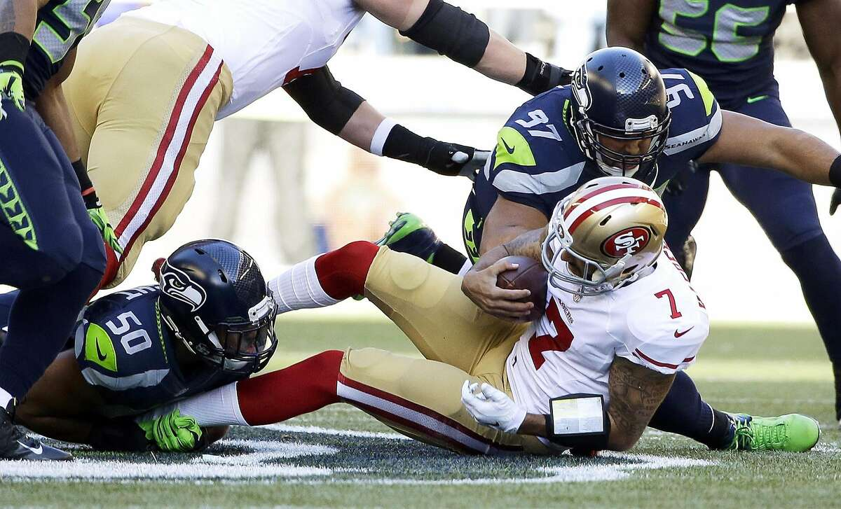 San Francisco 49ers quarterback Colin Kaepernick is sacked by Seattle Seahawks defensive tackle Jordan Hill (97) and outside linebacker K.J. Wright (50) in the first half of an NFL football game against the Seattle Seahawks, Sunday, Dec. 14, 2014, in Seattle. (AP Photo/Elaine Thompson)