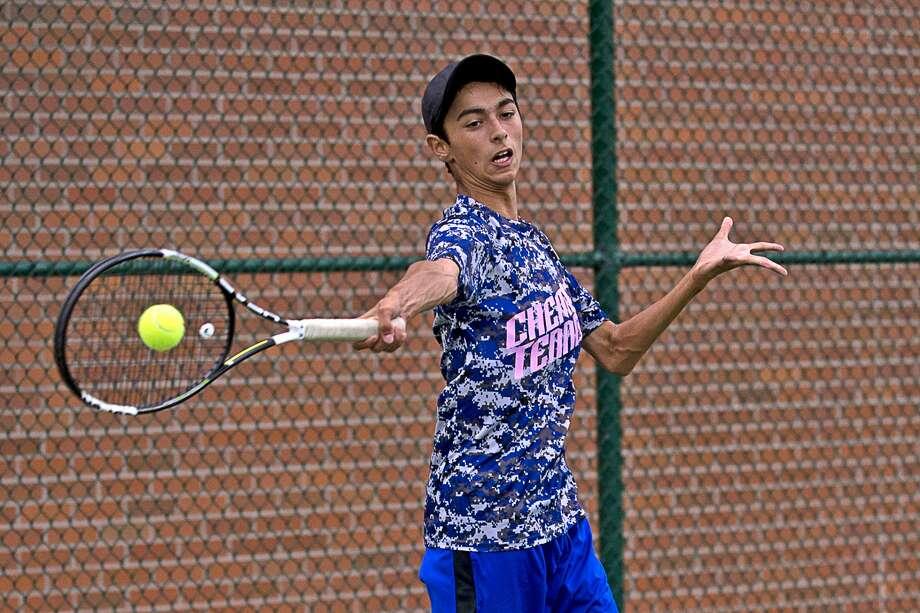 Midland's Brandon Johnson returns a serve during his No. 1 singles match on Thursday at H.H. Dow High School. Photo: Erin Kirkland/Midland Daily News