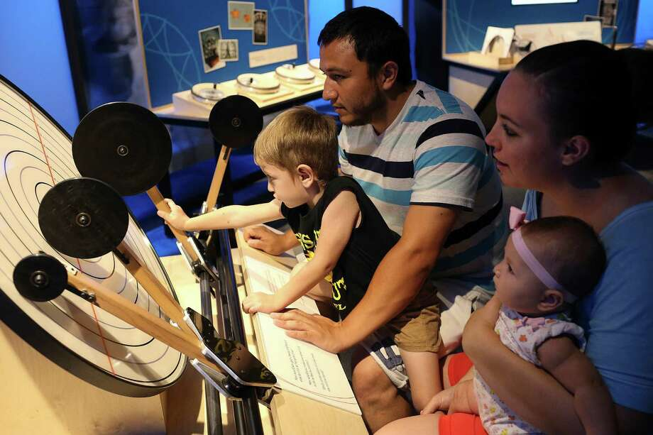 Liam Reyes, 3, plays with a game that explores frequencies at the Mathletics exhibit at the DoSeum on Aug. 28. The exhibit lets the public explore fundamental math concepts. With Reyes are from left, his father, Luis Reyes, 27, mother, Rebeka Reyes, 24 and sister, Spencer, 5-month-old. The family was on vacation from San Angelo. Photo: Jerry Lara /San Antonio Express-News / © 2016 San Antonio Express-News