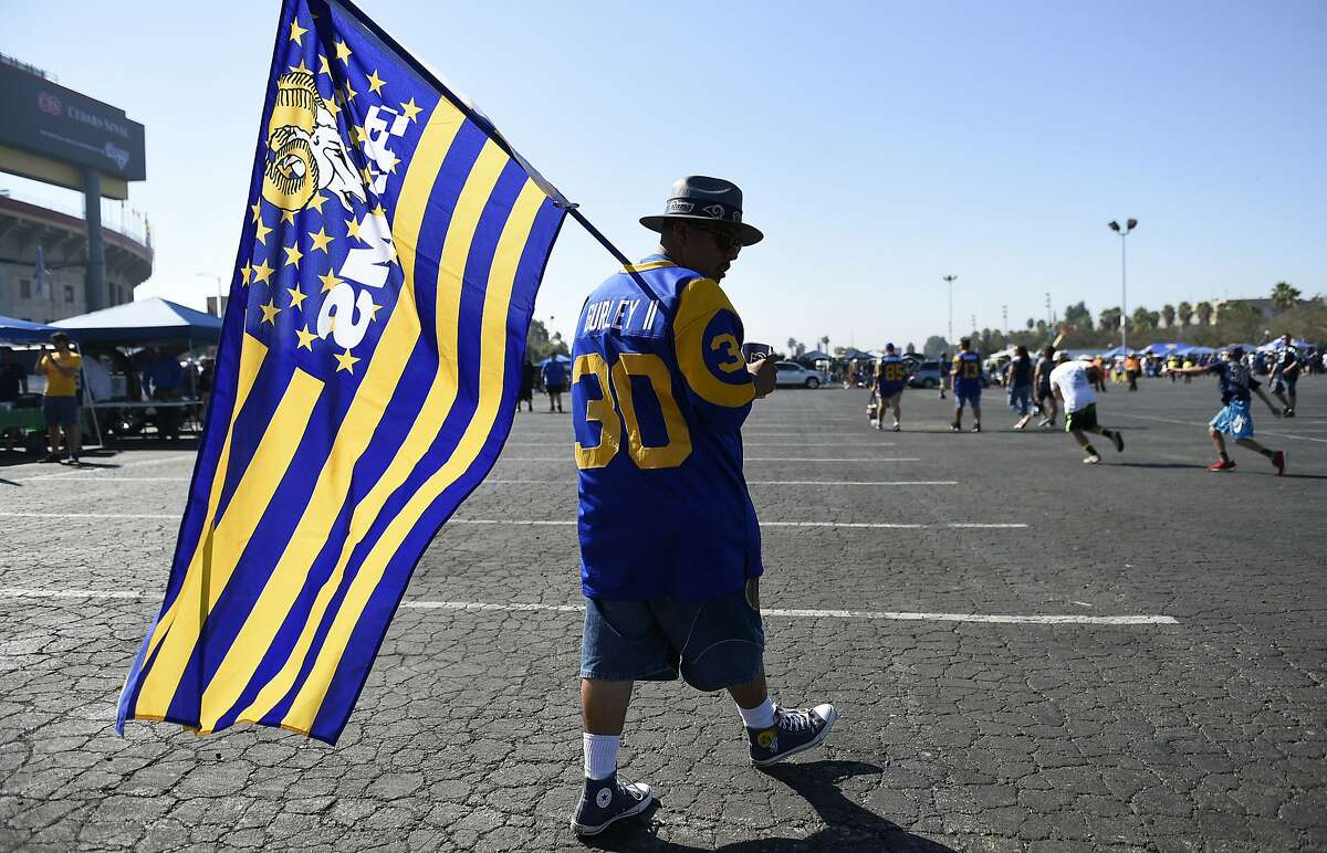 A fan walks the parking lot prior to an NFL football game between the Los Angeles Rams and the Seattle Seahawks at Los Angeles Memorial Coliseum, Sunday, Sept. 18, 2016, in Los Angeles. (AP Photo/Kelvin Kuo)